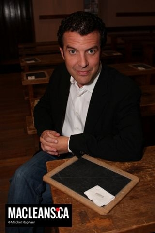 Rick Mercer sitting at a desk in The Schoolroom, with a slate and chalk in front of him